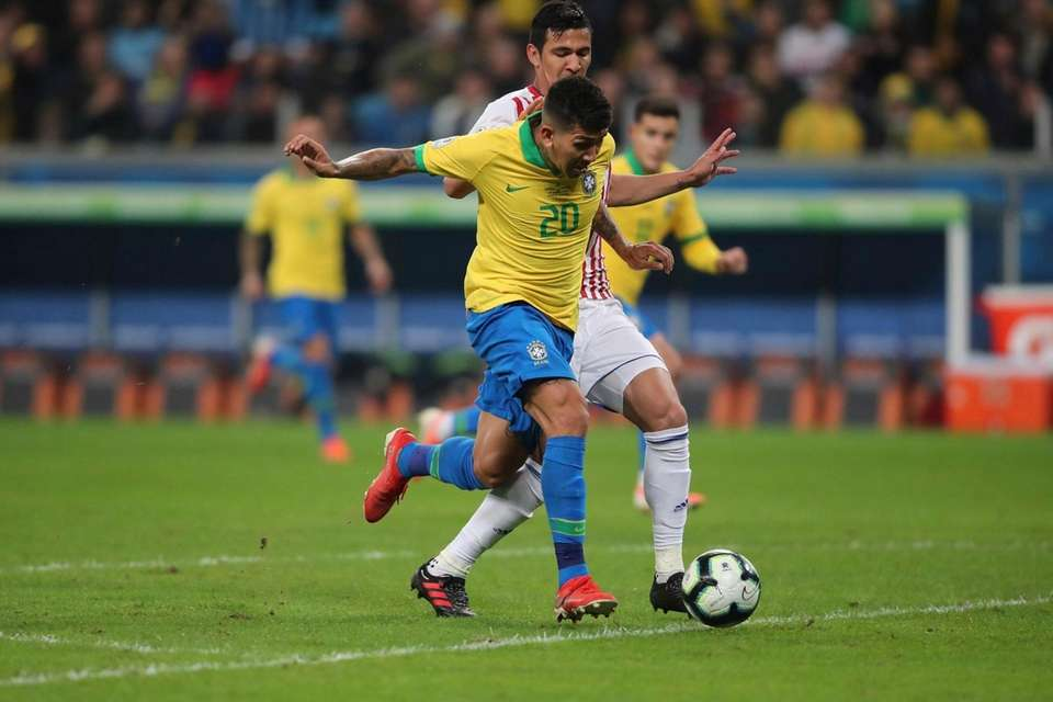 Brazil's Roberto Firmino (20) is tackled by Paraguay's