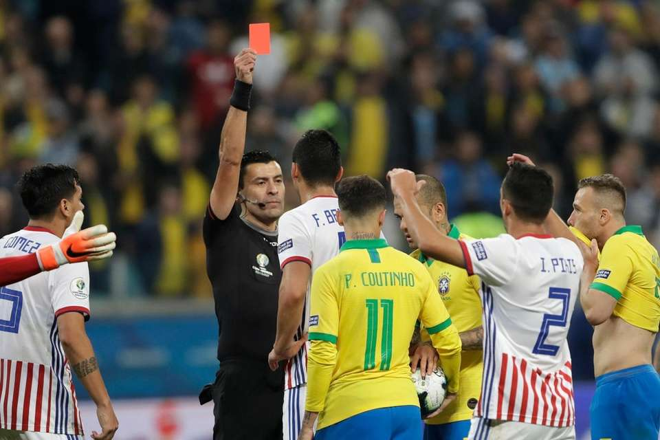 Referee Roberto Tobar shows the red card to