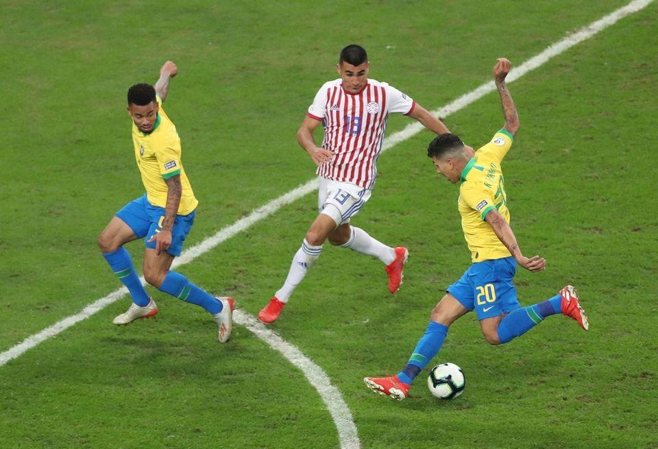 Brazil's Roberto Firmino, right, controls the ball past