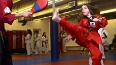 Michaela Rogers, 10, practices a kick at Martial