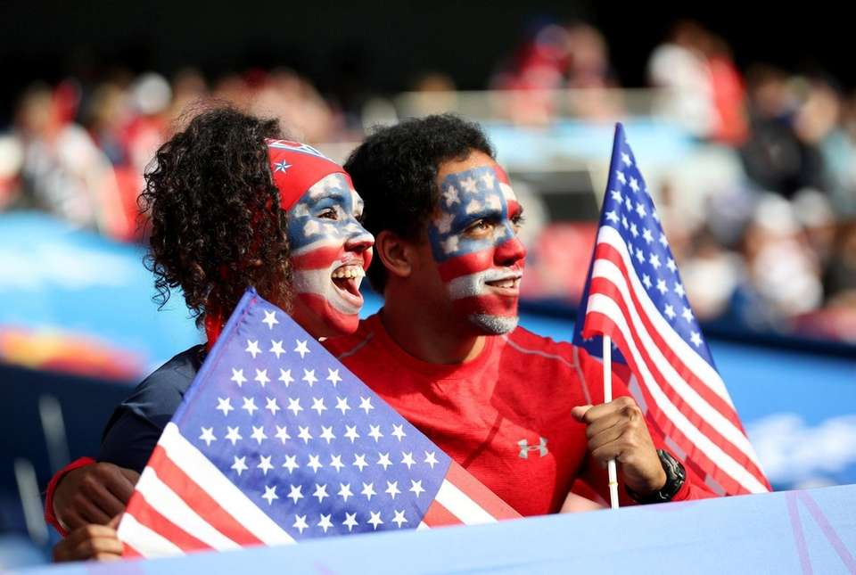 Fans for the U.S. hold U.S. flags and
