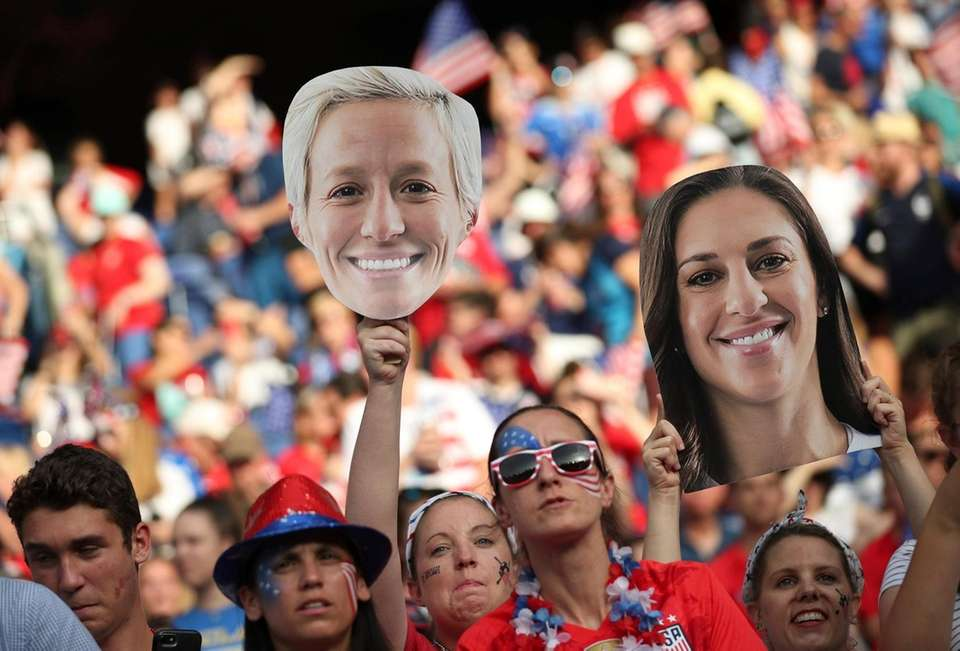 Fans for the U.S. hold up cards with