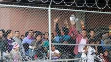 Central American migrants wait for food in a