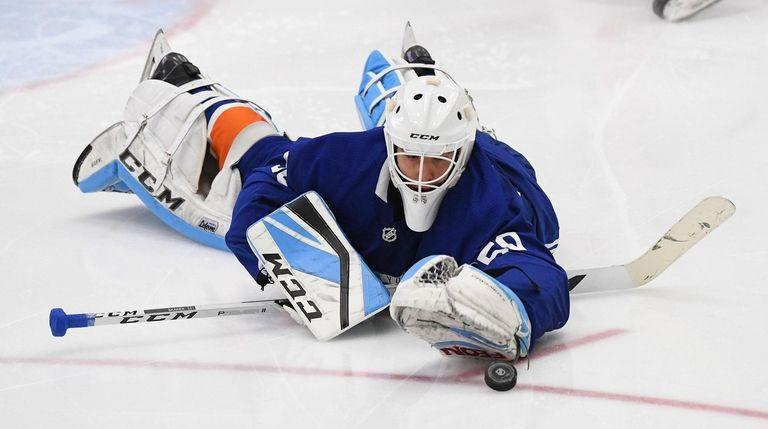Islanders goalie Jakub Skarek dives after the puck