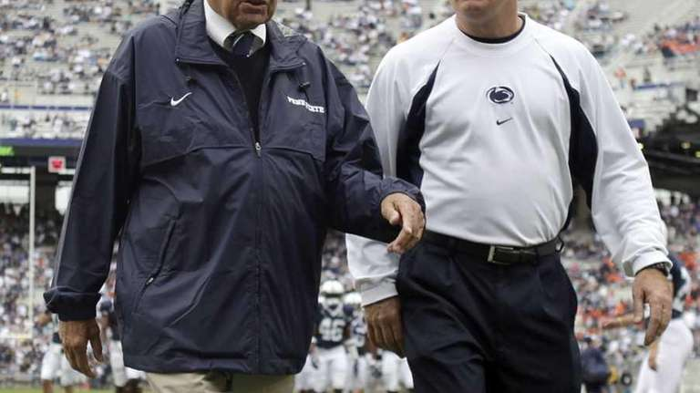 Joe Paterno, left, walks with assistant coach Tom