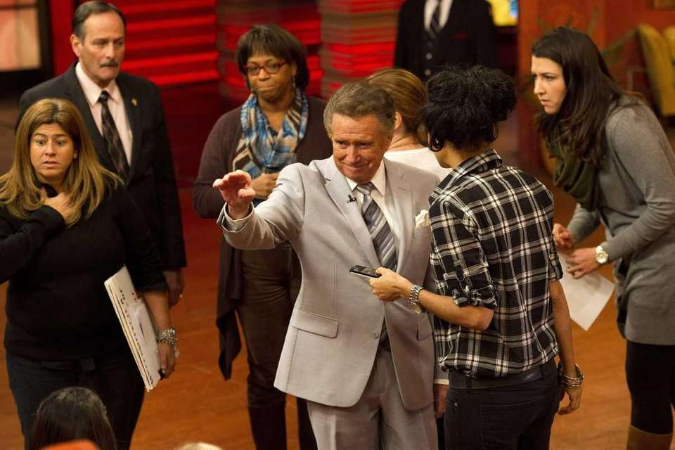 Regis Philbin, center, is surrounded by staffers as