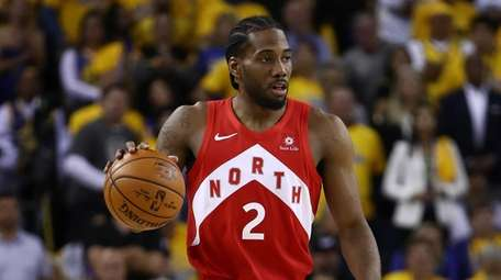 Kawhi Leonard of the Raptors handles the ball