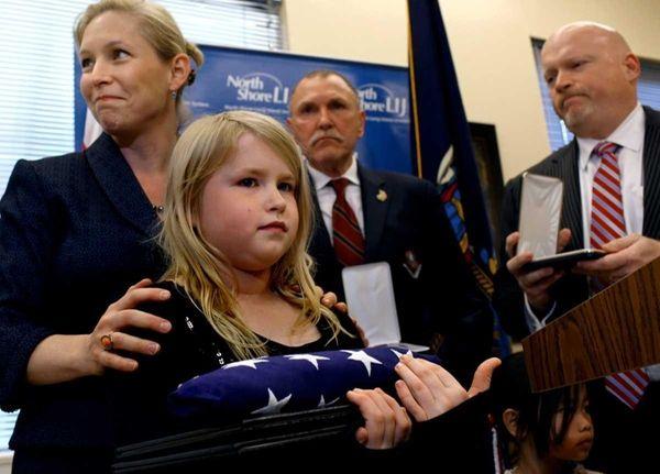 Riley Kaler, 8, holds a folded American Flag
