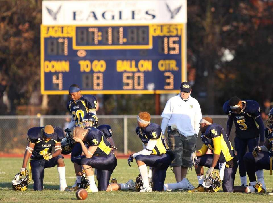 West Babylon football players take a knee as