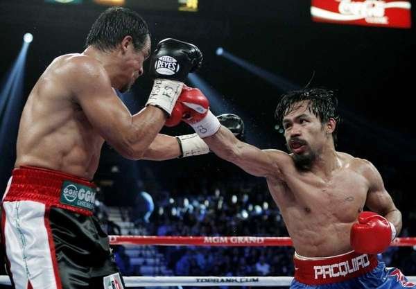 Manny Pacquiao, right, of the Philippines, hits Mexico's