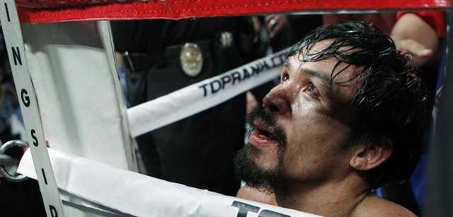 Manny Pacquiao, of the Philippines kneels in his