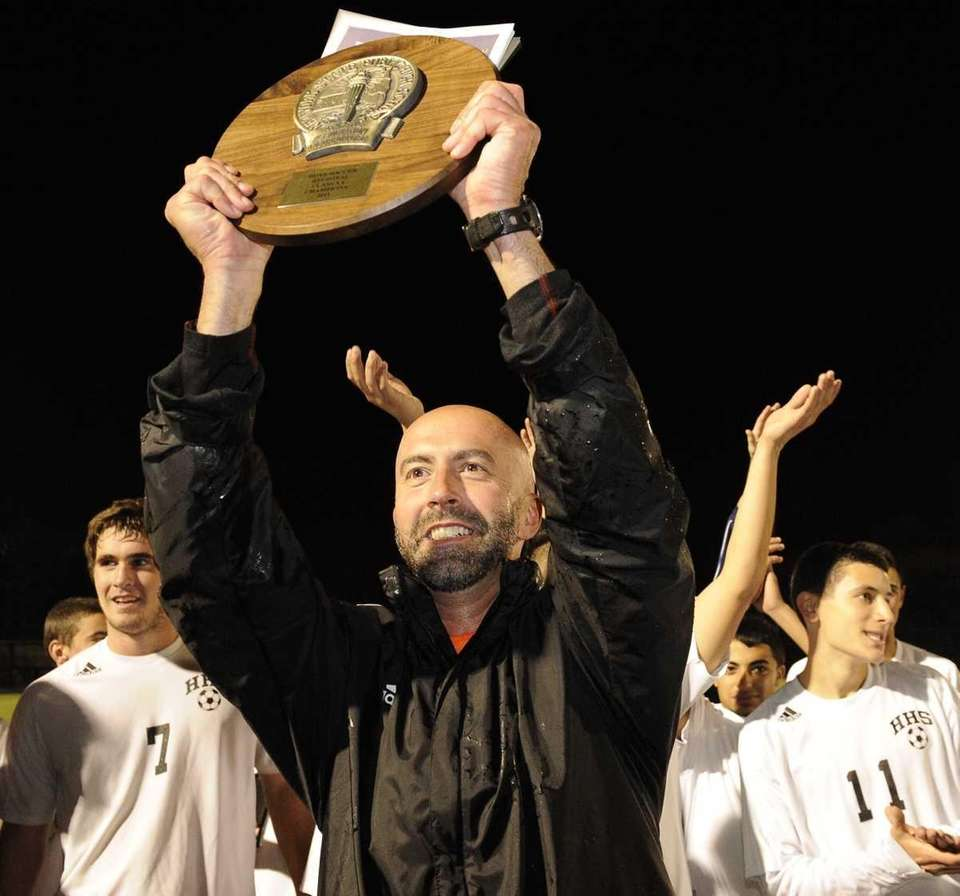 Hicksville's assistant coach Jack Fabrizio holds up the