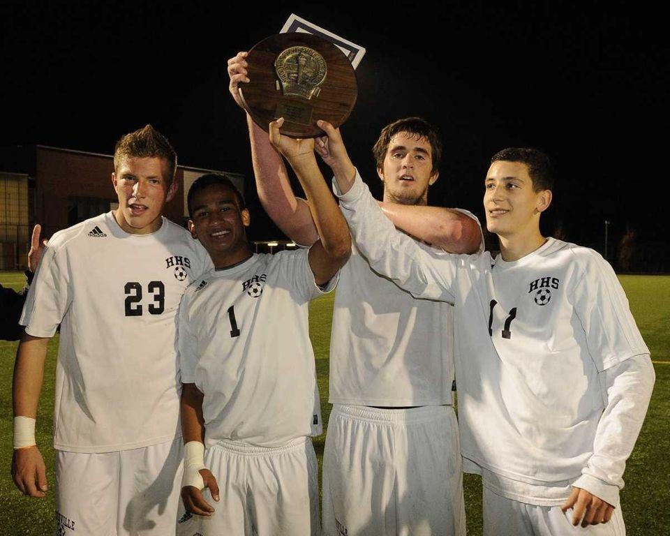 Hicksville teammates raise their championship plaque, from left