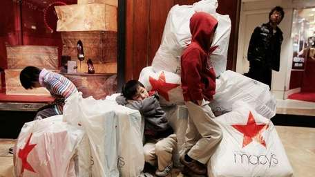 Children wait with shopping bags inside Macy's on