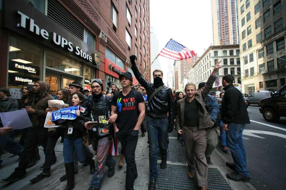 Occupy Wall Street demonstrators march down Broadway as