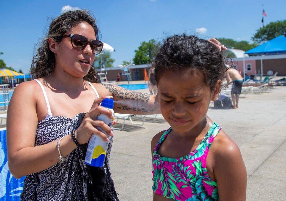 Fran puts sunblock on her daughter Annabelle Durden,