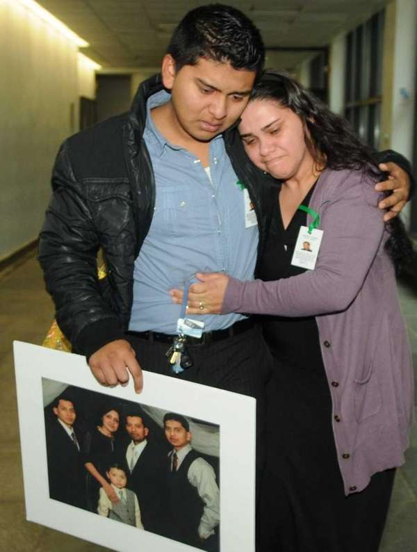 Denis Caceres is comforted by family friend Ivonne