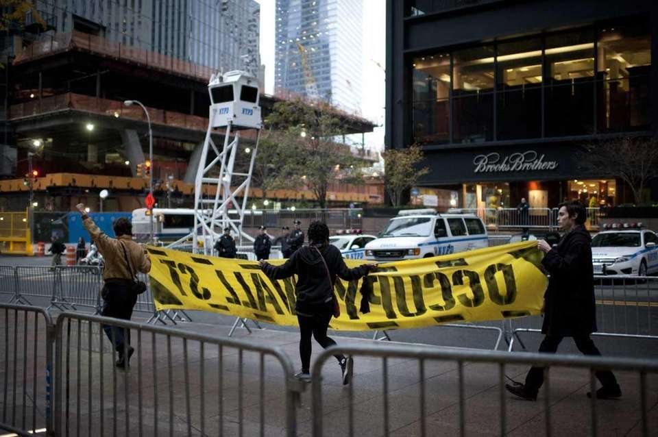 Occupy Wall Street demonstrators walk the perimeter of