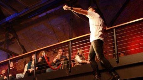 Ryan Star climbs the balcony at his show