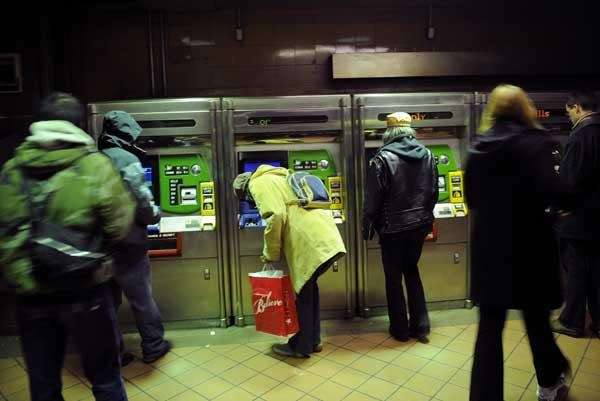Commuters buy subway passes at a subway station