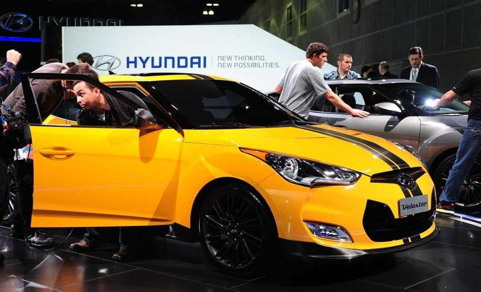 A man steps out of a Hyundai Veloster