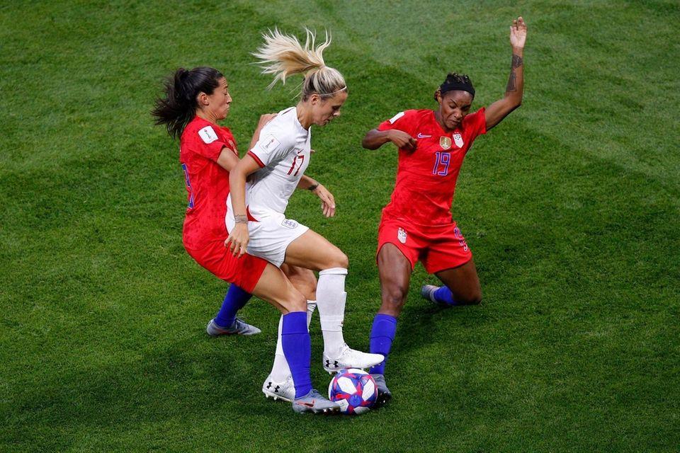 England's Rachel Daly, center, controls the ball as