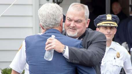 Suffolk County Executive Steve Bellone consoles Phillip Alvarez,