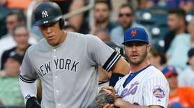 Yankees rightfielder Aaron Judge stands next to Mets