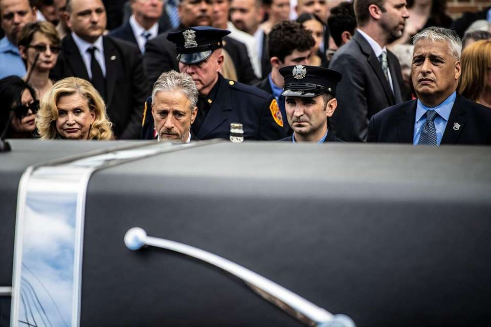 Jon Stewart  stands as the casket goes