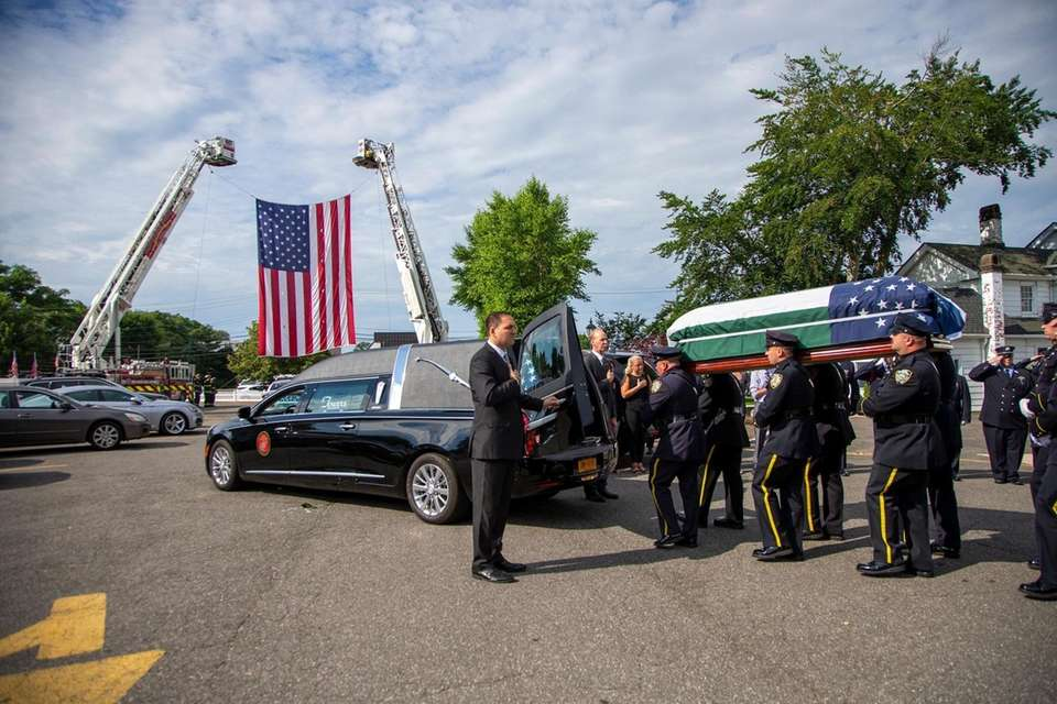 Officers carry NYPD Det. Luis Alvarez's coffin out