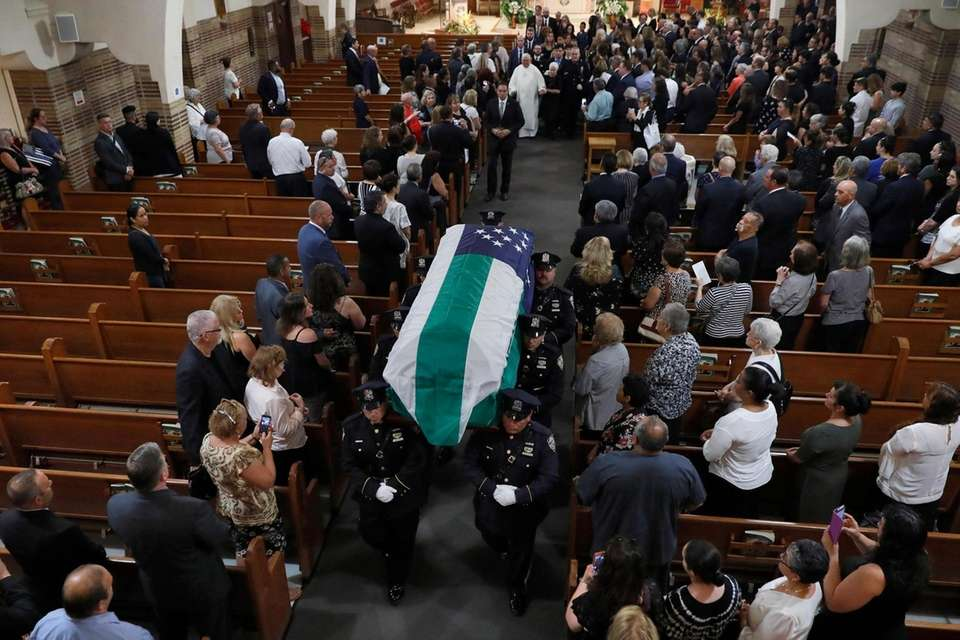 The casket of Detective Luis Alvarez is carried