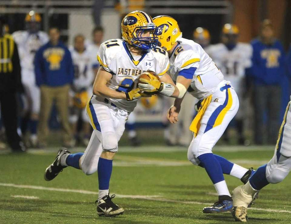 East Meadow's Robbie Healy, left, takes a hand-off