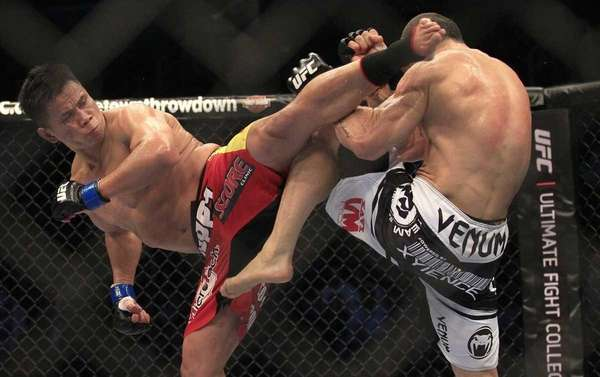 Cung Le, left, kicks Wanderlei Silva during the