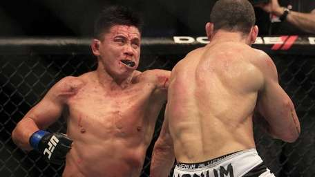 Cung Le, left, punches Wanderlei Silva, for Brazil,