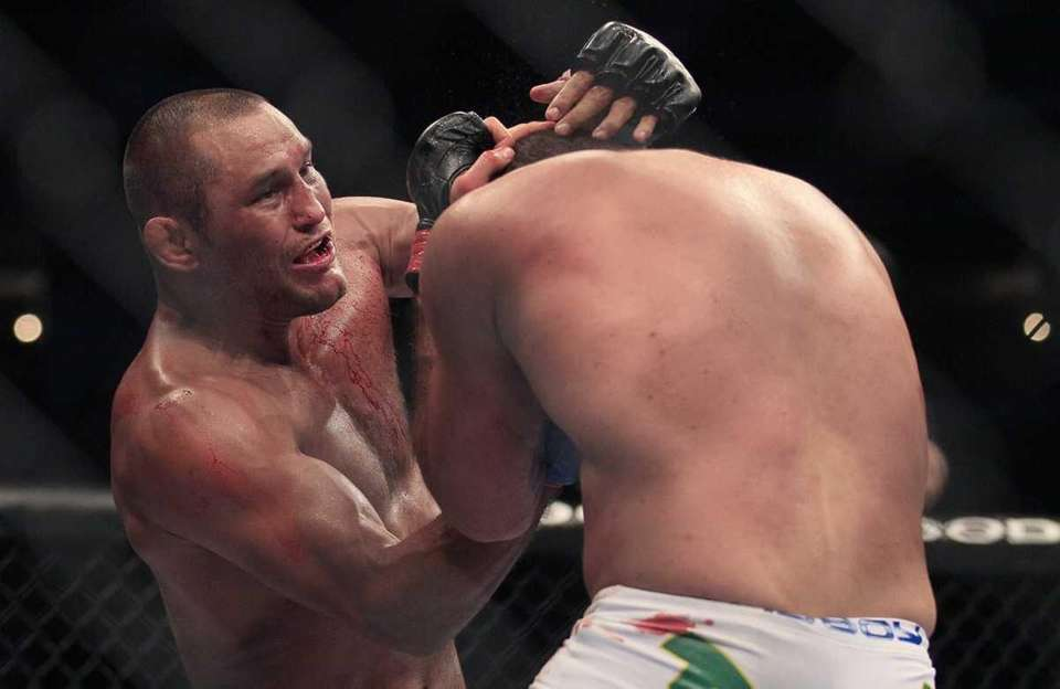 Dan Henderson, top, punches Mauricio Rua during the
