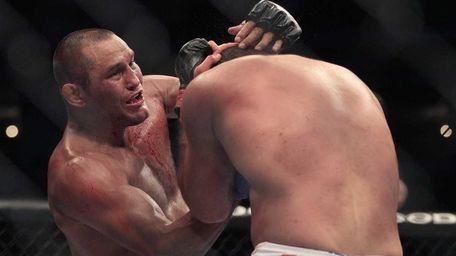 Dan Henderson, top, punches Mauricio Rua during the