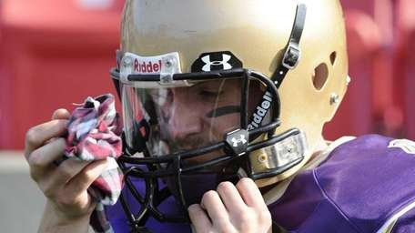 Sayville quarterback Steven Ferreira wipes his visor during