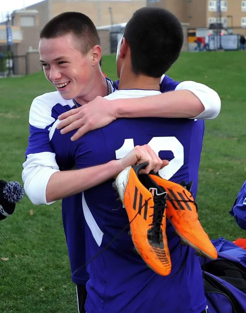 Port Jefferson's Harry Colucci, facing, hugs teammate Gabe
