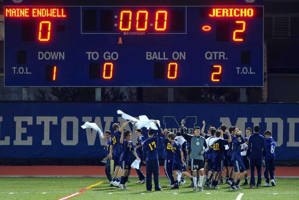 Jericho players celebrate in front of the scoreboard