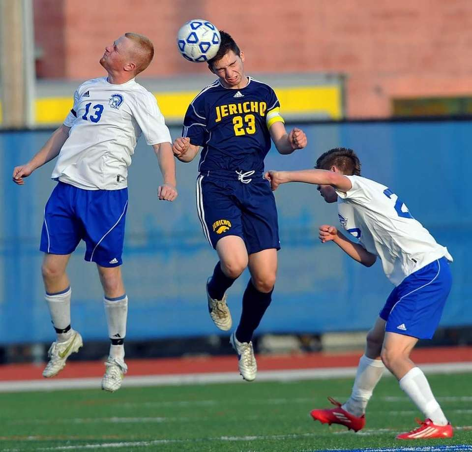 Jericho's Harrison Reiber, center, wins the header between