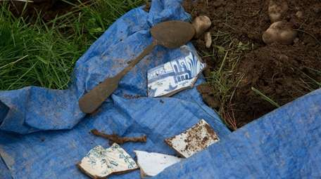 A spoon and pieces of ceramic unearthed during