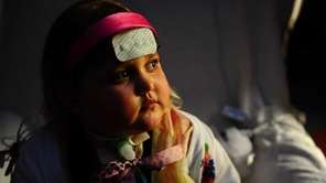 Marisa Carney, 5, sits in a hospital room