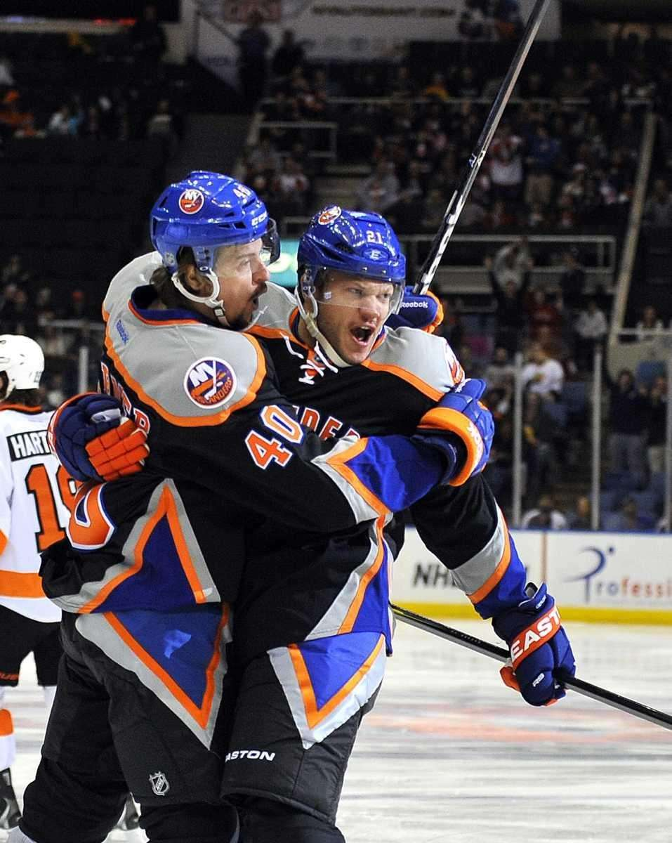 Kyle Okposo, right, gets a congratulatory hug from