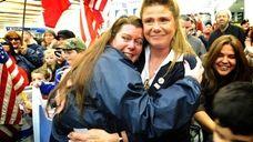 Rosemarie Fitzpatrick, left, embraces Cynthia Ventura, right, president