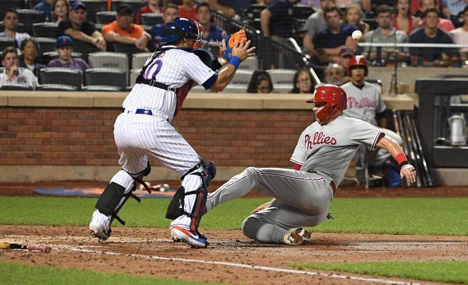 Philadelphia Phillies' Rhys Hoskins slides to score before