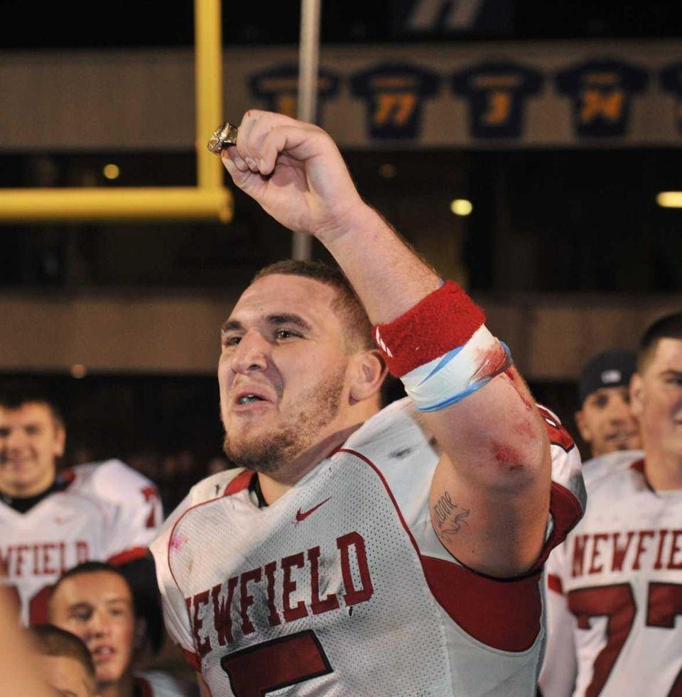 Newfield's Ron Denig holds aloft the Superbowl XXXV