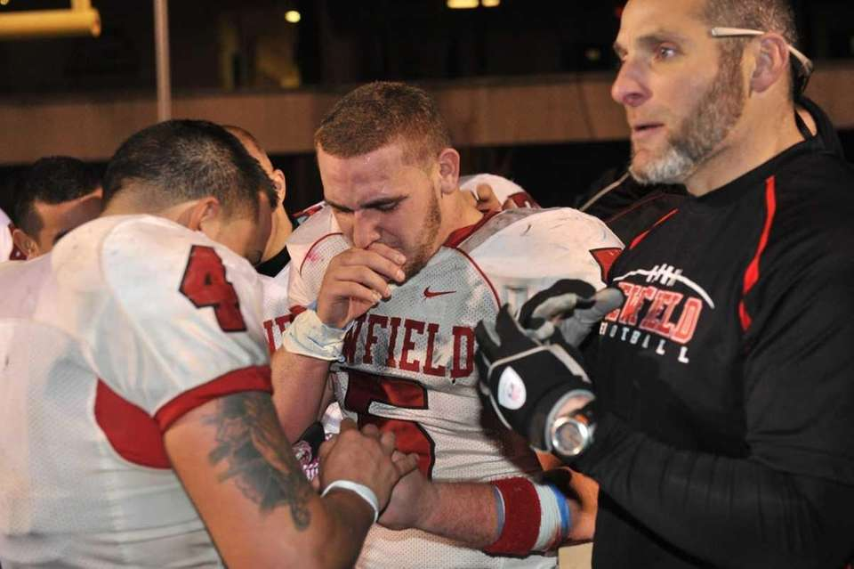 Newfield's Ron Denig cries while passing around the