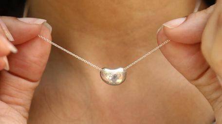 Lisa Calla shows a silver necklace with a