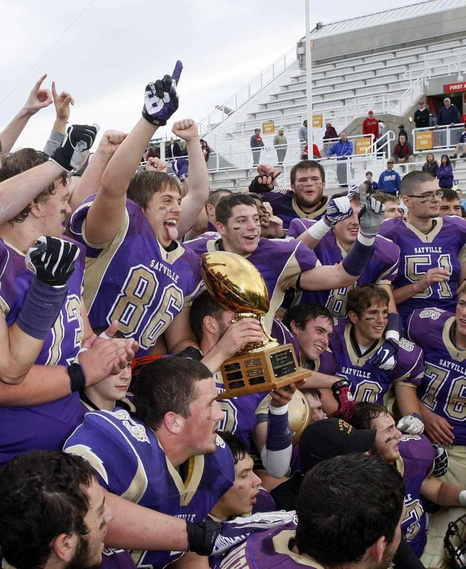 The Sayville football team hold their trophies after