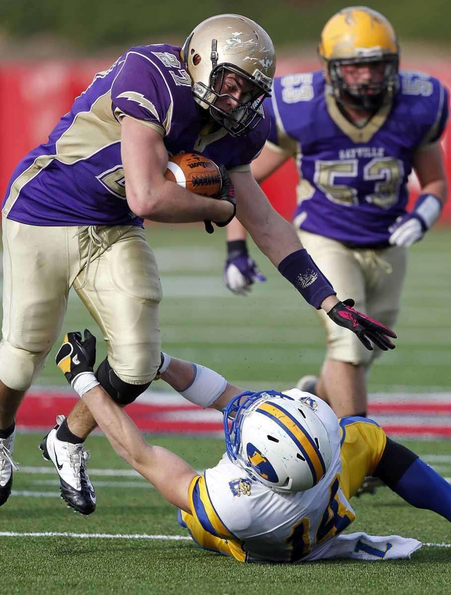 Sayville's John Haggart (27) runs over Lawrence linebakcer